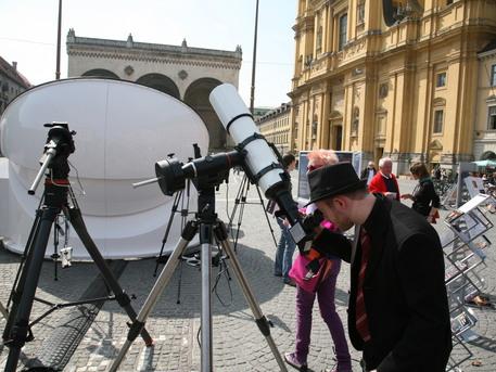 Die ersten Passanten schauen durch die auf dem Odeonsplatz aufgebauten Teleskope in die Sonne.