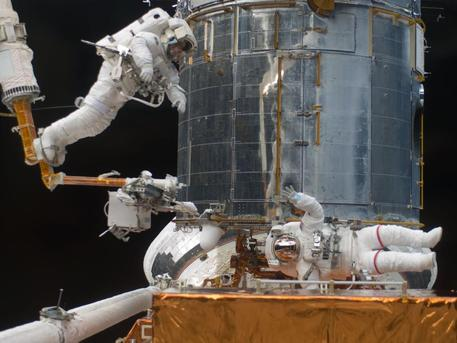 The picture was taken during the third spacewalk and shows the astronauts working on the giant telescope.