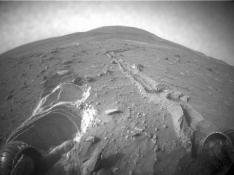 """Viel lockerer und tiefer als die Experten es vermutet hatten, ist der Sand durch den der Marsrover Spirit derzeit fährt. Diese Aufnahme machte die """"Hazard Identification Camera"""" am 26. April 2009. Experten beraten derzeit, wie sie verhindern können, dass der Marsrover immer tiefer in den Sand einsinkt."""