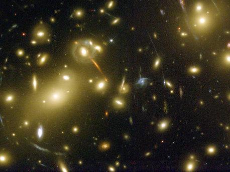 Gravitation kann Licht beugen, weshalb große Galaxienhaufen als Teleskope fungieren können. Fast alle hellen Objekte auf dieser Aufnahme des Hubble-Weltraumteleskops sind Galaxien des als Abell 2218 bekannten Haufens. Der Haufen ist so massereich und so kompakt, dass seine Gravitation das Licht der Galalaxien, die dahinter liegen, krümmt und fokussiert. Ein Ergebnis daraus ist, dass Mehrfachbilder dieser Hintergrundgalaxien zu langen, blassen Bögen verzerrt werden - ein einfacher Linseneffekt, den man mit dem Betrachten weit entfernter Straßenlampen durch ein Weinglas vergleichen kann.