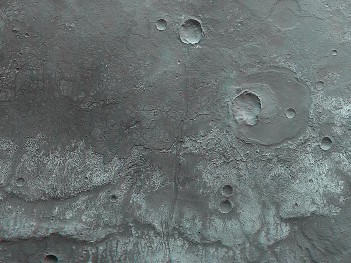 """Aus dem senkrecht auf den Mars blickenden Nadirkanal des Kamerasystems HRSC auf der ESA-Sonde Mars Express und einem der vier schräg auf die Marsoberfläche gerichteten Stereokanäle lassen sich so genannte Anaglyphenbilder erzeugen, die bei Verwendung einer Rot-Blau-(Cyan)- oder Rot-Grün-Brille einen dreidimensionalen Eindruck der Landschaft vermitteln; Norden ist rechts im Bild.  Dieses Gebiet im Südosten des Marscanyons Ma'adim Vallis ist von ausgedehnten, erkalteten Lavaströmen gekennzeichnet. In der 3D-Betrachtung erkennt man, wie die vorderen Fließfronten von Lavaströmen aus Basalt an so genannten """"Runzelrücken"""" enden, die über viele Kilometer eine Geländestufe zu den tiefer gelegenen Lavadecken ausbilden.  Im nördlichen Teil des Gebietes, rechts der Bildmitte, ist ein etwa 20 Kilometer großer Einschlagkrater zu erkennen. Dieser Krater wurde von Lava zu einem großen Teil verfüllt, ist also früher als der Lavastrom entstanden. Später bildete sich durch einen weiteren Einschlag ein kleinerer, etwa sieben Kilometer großer Krater im südlichen Teil des alten Kraters. Durch die Bildmitte verläuft in Ost-West-Richtung, also von unten nach oben, eine insgesamt mehr als 200 Kilometer lange Störungszone."""