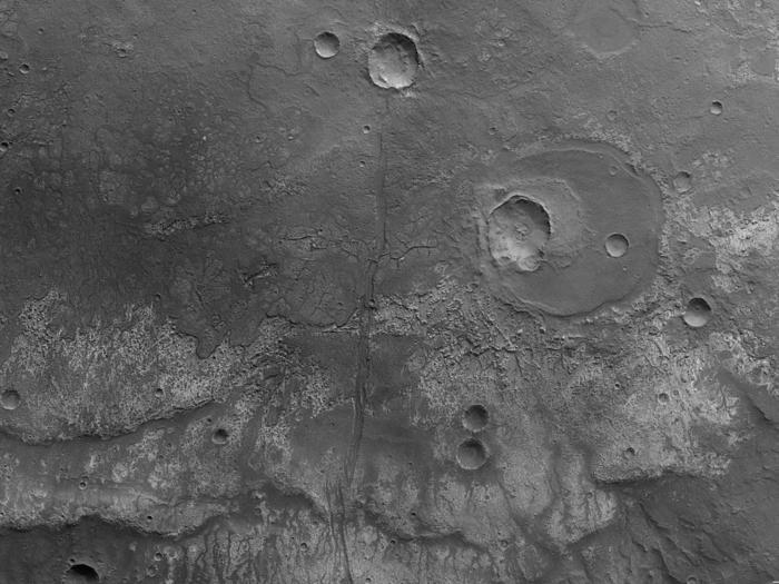 """Der senkrecht auf die Marsoberfläche gerichtete Nadirkanal liefert die höchste Auflösung des Kamerasystems HRSC (High Resolution Stereo Camera) auf der ESA-Raumsonde Mars Express. Während Orbit 6393 nahm die HRSC am Heiligabend 2008 ein Gebiet südöstlich des Marscanyons Ma'adim Vallis aus einer Höhe von etwa 325 Kilometern in einer Auflösung von 15 Metern pro Bildpunkt (Pixel) auf. Die Abbildungen zeigen hiervon einen etwa 140 Kilometer mal 70 Kilometer großen Ausschnitt bei 29 Grad südlicher Breite und 182 Grad östlicher Länge; Norden ist rechts im Bild.  Das Gebiet ist von ausgedehnten, erkalteten Lavaströmen gekennzeichnet. Bei dem etwa quer durch die Bildmitte verlaufenden Übergang von dunklem Material im Westen der Region (obere Bildhälfte) zu hellerem Material im unteren Bildteil handelt es sich um die vordere Fließfront eines Lavastroms aus Basalt.  Gut sind im Osten (untere Bildhälfte) der Lavadecke so genannte """"Runzelrücken"""" zu erkennen, die über viele Kilometer eine Geländestufe zu den tiefer gelegenen Lavadecken ausbilden.  Im nördlichen Teil des Gebietes, rechts der Bildmitte, ist ein etwa 20 Kilometer großer Einschlagkrater zu erkennen. Dieser Krater wurde von Lava zu einem großen Teil verfüllt, ist also früher als der Lavastrom entstanden. Später bildete sich durch einen weiteren Einschlag ein kleinerer, etwa sieben Kilometer großer Krater im südlichen Teil des alten Kraters. Durch die Bildmitte verläuft in Ost-West-Richtung, also von unten nach oben, eine insgesamt über 200 Kilometer lange Störungszone."""