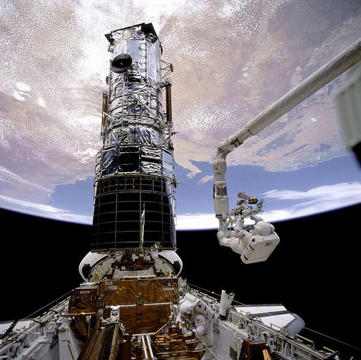 Der Astronaut Story Musgrave an der Spitze des Roboterarms bereitet sich auf die erste Service Mission des Hubble Weltraumteleskops vor
