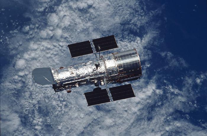 Das Hubble Weltraumteleskop über der Erdoberfläche, fotografiert vom Space Shuttle aus