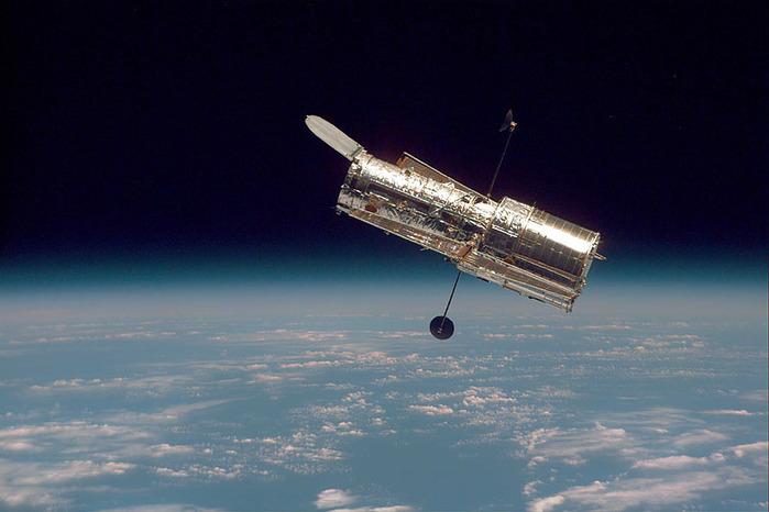 Das Hubble Weltraumteleskop von der Seite oberhalb der dünnen Erdatmosphäre