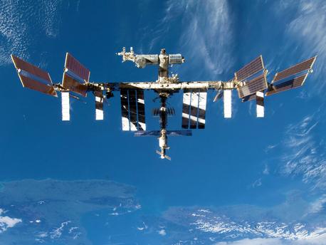 Die Internationale Raumstation ISS am 8. September 2009 nach dem Abdockmanöver des Space Shuttles Discovery. Das Bild zeigt die ISS vor blau-weißer Erde.