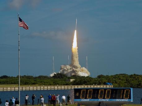 The stars and stripes on the American flag reflect NASA's commitment to teamwork as the Constellation Program's Ares I-X test rocket roars off Launch Complex 39B at NASA's Kennedy Space Center in Florida.