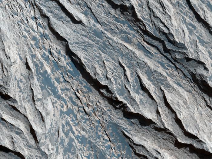 Mineralische Schichten in Candor Chasma. Diese Aufnahme zeigt eine Felsklippe im Valles Marineris. Wind-Erosion hat scharfe, V-förmige Muster in die Schichten eingeprägt.