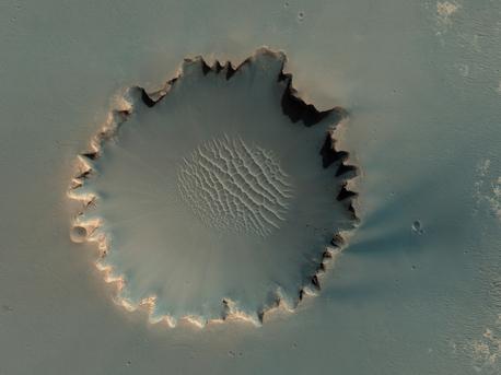 Der Victoria-Krater im Hochland Meridiani Planum. Er besitzt einen Durchmesser von etwa 800 Metern. Sedimentschichten und Felsen sind an seinem inneren Rand auszumachen. Letztere sind zum Teil sogar in das Zentrum des Kraters hinabgefallen. Der NASA Mars Rover Opportunity hat diesen Krater vor einigen Jahren besucht und untersucht.