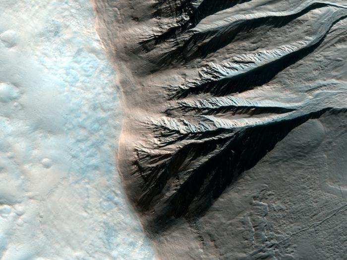 Der Rand eines etwa sechs Kilometer großen Kraters auf der südlichen Halbkugel. man erkennt Abflußrinnen, die zum Kraterboden hinab führen.