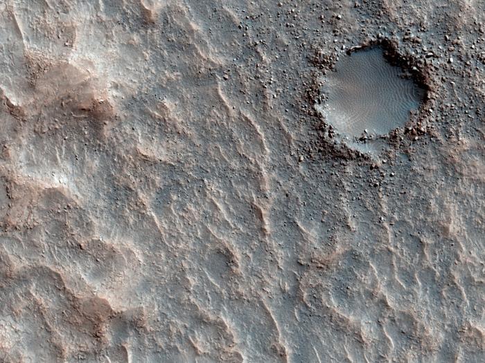 Ein kleiner Einschlagskrater, an dessen Rändern Ejekta vom Einschlag zu finden sind. Diese sind bereits mit Sand verfüllt.