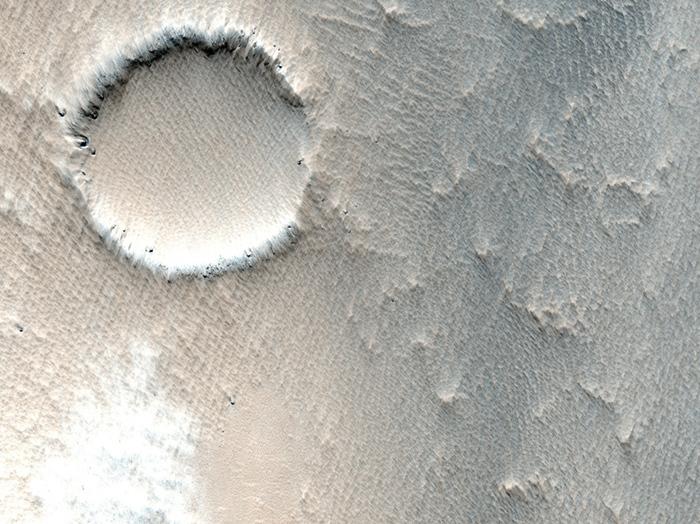 Ein kleiner Krater, der zum Teil schon von Ejekta aus anderen Einschlägen zugeweht wurde.