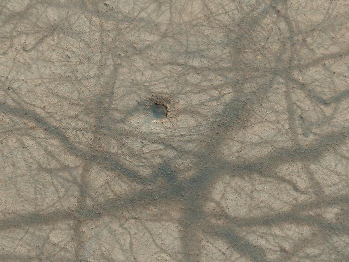 Ein winziger Einschlagskrater und ein Ineinandergreifen  verschiedener Staub-Teufel-Pfade auf der Marsoberfläche.