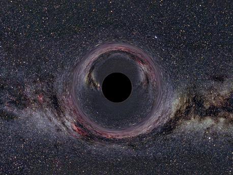 Das computersimulierte Bild zeigt ein fiktives Schwarzes Loch von 10 Sonnenmassen aus 600 Kilometer Abstand. Die Milchstraße im Hintergrund erscheint durch die Raumkrümmung verzerrt und doppelt.