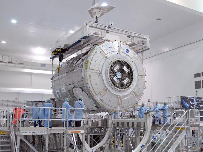 In der Vorbereitungshalle (Space Station Processing Facility) am Kennedy Space Center der amerikanischen Weltraumbehörde NASA in Florida wird Tranquility (Node 3) in eine Arbeitsvorrichtung während der Missionsvorbereitungen verladen.