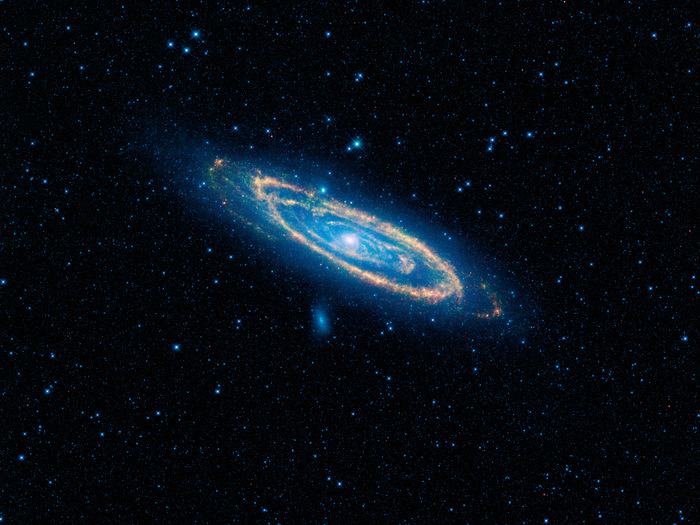 The immense Andromeda galaxy, also known as Messier 31 or simply M31, is captured in full in this new image from WISE. The mosaic covers an area equivalent to more than 100 full moons, or five degrees across the sky. WISE used all four of its infrared detectors to capture this picture (3.4- and 4.6-micron light is colored blue; 12-micron light is green; and 22-micron light is red). Blue highlights mature stars, while yellow and red show dust heated by newborn, massive stars.