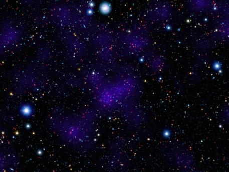 A surprisingly large collection of galaxies (red dots in center) stands out at a remarkably large distance in this composite image combining infrared and visible-light observations. NASA's Spitzer Space Telescope contributed to the infrared component of the observations, while shorter-wavelength infrared and visible data are provided by Japan's Subaru telescope atop Mauna Kea, Hawaii.