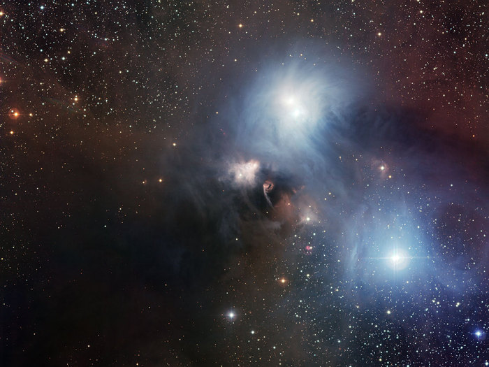 The nearby star-forming region around the star R Coronae Australis imaged by the Wide Field Imager (WFI) on the MPG/ESO 2.2-metre telescope at ESO's La Silla Observatory in Chile. This picture, which covers a field of 33.7 x 31.9 arcminutes (about the diameter of the full Moon), is a combination of twelve CCD frames, 67 megapixels each, taken through B, V and R filters, with four exposures of five minutes each.