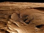 Aus den schräg auf die Oberfläche gerichteten Stereo- und Farbkanälen des Kamerasystems HRSC auf Mars Express können realistische, perspektivische Ansichten der Marsoberfläche erzeugt werden. Das Bild zeigt einen Blick etwa von Westen nach Osten auf einen etwa 42 Kilometer großen Krater, der durch den Einschlag eines Asteroiden auf dem Rand des viel größeren Kraters Schiaparelli (Durchmesser 460 Kilometer) gebildet wurde.  Das Innere dieses fast 2000 Meter tiefen Kraters ist mit Sedimenten verfüllt. Genau im Zentrum ist eine Struktur zu erkennen, die einem Flussdelta ähnelt. Diese Struktur scheint zum Teil aus gerundeten, hellen, durch die Erosion von Wind und Wasser veränderten Hügeln zu bestehen. Dunkles, ebenfalls durch den Wind transportiertes Material wurde vorzugsweise im südlichen Teil des Kraters abgelagert. Dünenfelder aus dunklem, zum Teil fast schwarzem Material, die das Plateau im Zentrum des Kraters sichelförmig umgeben, verdeutlichen hier wiederum große Materialumlagerungen durch Wind.