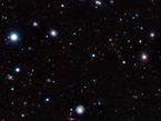 """Mit einer ganzen Armada von Teleskopen auf dem Erdboden und im Weltall, unter anderem dem Very Large Telescope der ESO am Paranal-Observatorium in Chile, haben Astronomen den am weitesten entfernten bislang bekannten """"erwachsenen"""" Galaxienhaufen entdeckt und seine Entfernung zur Erde bestimmt. Das Licht, das sie dafür aufgefangen haben, stammt aus einer Zeit, als das Universum weniger als ein Viertel so alt war wie jetzt. Der junge Haufen zeigt überraschend große Ähnlichkeit mit den Galaxienhaufen im heutigen Universum, die ungleich mehr Zeit hatten, sich weiter zu entwickeln."""
