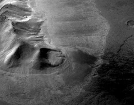 Gebirge in der östlichen Hellas-Region: Der Höhenzug ist umgeben von Ablagerungen mit Fließtexturen auf der Oberfläche. Bodenradarmessungen haben nun gezeigt, dass es sich um einen Gletscher handelt, der unter einer dünnen Gesteinslage begraben liegt.