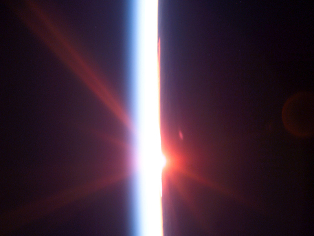 This view featuring a sunrise dissecting a line of airglow of Earth's atmosphere was photographed by an STS-114 crewmember onboard Space Shuttle Discovery after departure from the International Space Station.