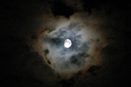 Dünne Wolken mit einem Hof um den Mond