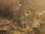 """Diese senkrechte Farb-Draufsicht auf ein Gebiet südöstlich des Marscanyons Ma'adim Vallis im Marshochland wurde aus dem senkrecht blickenden Nadirkanal und den schräg auf die Oberfläche gerichteten Farbkanälen des Kamerasystems HRSC erstellt; Norden ist rechts im Bild.  Das Gebiet ist von ausgedehnten, erkalteten Lavaströmen gekennzeichnet. In der Farbdarstellung lässt sich gut ein etwa quer durch die Bildmitte verlaufender Übergang von dunklem Material im Westen der Region (obere Bildhälfte) zu hellerem Material im unteren Bildteil beobachten. Dabei handelt es sich um die vordere Fließfront eines Lavastroms aus Basalt.  In der unteren Bildhälfte sind östlich der Fließfronten der Lavadecken so genannte """"Runzelrücken"""" zu erkennen, die über viele Kilometer eine Geländestufe zu den tiefer gelegenen Lavadecken ausbilden.  Im nördlichen Teil des Gebietes, rechts der Bildmitte, ist ein etwa 20 Kilometer großer Einschlagkrater zu erkennen. Dieser Krater wurde von Lava zu einem großen Teil verfüllt, ist also früher als der Lavastrom entstanden. Später bildete sich durch einen weiteren Einschlag ein kleinerer, etwa sieben Kilometer großer Krater im südlichen Teil des alten Kraters. Durch die Bildmitte verläuft in Ost-West-Richtung, also von unten nach oben, eine insgesamt über 200 Kilometer lange Störungszone."""