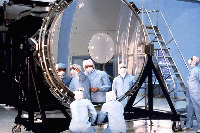 Techniker begutachten den 2,4 Meter großen Hauptspiegel von Hubble