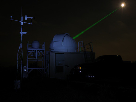 Goddard's Laser Ranging Facility directing a laser (green beam) toward the LRO spacecraft in orbit around the moon (white disk). The moon has been deliberately over-exposed to show the laser.