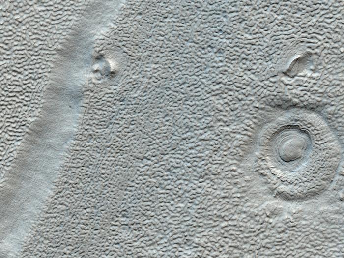 Dieses Bild zeigt eine Talverfüllung und Schutt-Schürzen im Deuteronilus Mensae Gebiet. Viele der Talfußböden in diesem Gebiet bestehen aus komplizierte Anordnungen von kleinen Kämmen und Gruben. Die Ursache der kleinen Textur ist nicht gut verstanden, kann sich aber aus Mustern in eisreichen Böden ergeben haben.