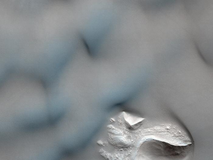 Dünen in einem Krater im Newton-Becken, die erodiert sind oder eine zusammenhängendere Felsstruktur bedecken.