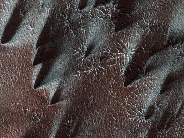 """Das südliche Polargebiet des Mars wird jedes Jahr durch eine Schicht Kohlendioxid-Eis bedeckt. In einem Gebiet mit Namen """"rätselhaftes Terrain,"""" ist das Eis lichtdurchlässig und so kann Sonnenlicht durch das Eis eindringen, um die Oberfläche von unten zu wärmen. Das Eisschicht-Sublimat verdampft vom Boden her."""