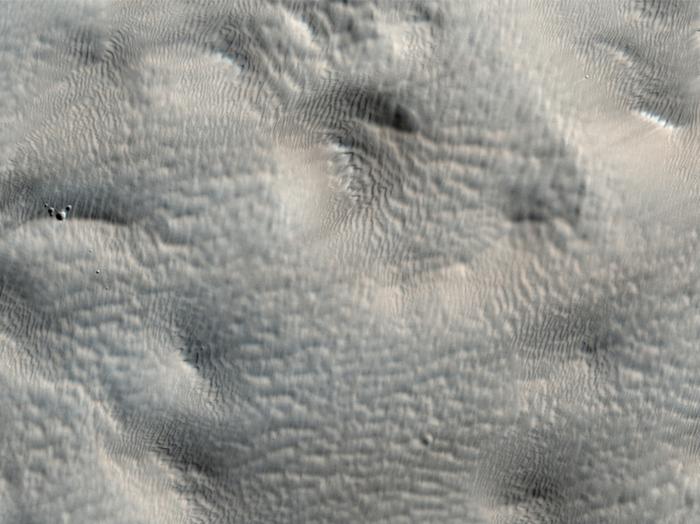 Kraus aussehende Landschaft nahe der Tharsis Montes (Tharsis-Berge). Einige Teile dieses Bildes können auf den ersten Blick unscharf erscheinen. Jedoch zeigen schare Bereiche des Bildes (wie die sichtbaren Krater), dass der krause Blick nicht ein Bildrelikt ist, sondern ein Zeichen für eine äußerst glatte Oberfläche. Der Grund für diese Glätte ist eine dicke Schicht von Staub, die die Landschaft zudeckt.