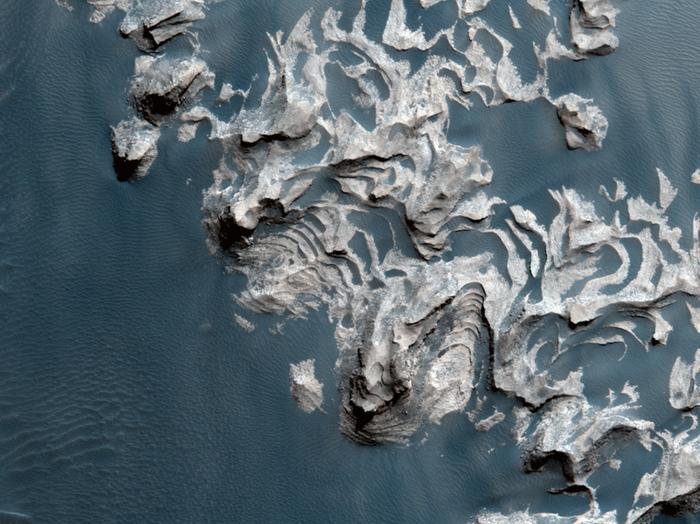 Ein großes, herausstehendes Gebiet aus geschichtetem Fels in der Region Aureum Chaos.