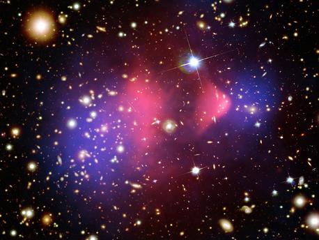 """Im Jahr 2006 entdeckten Astronomen einen ähnlichen Unfall im Universum. Da das heiße Gas (rosa) in der rechten Bildhälfte an eine Gewehrkugel erinnert, taufte man den Galaxienhaufen """"Bullet-Cluster"""", was soviel heisst wie Geschosshaufen"""