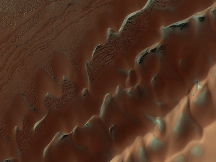 Dunes are often found on crater floors. In the winter time at high northern latitudes the terrain is covered by carbon dioxide ice (dry ice). In the spring as this seasonal ice evaporates many unusual features unique to Mars are visible.