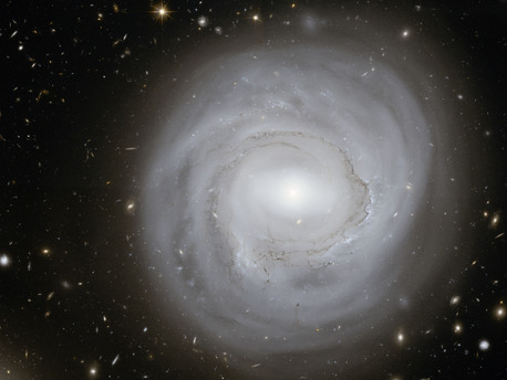 Esta imagen tomada con el Telescopio Espacial Hubble de la NASA / ESA,  muestra la galaxia espiral NGC 4921, junto con un espectacular telón de fondo de las galaxias más distantes.