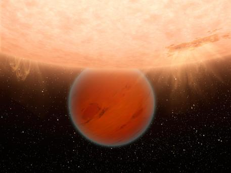 An unusual, methane-free world is partially eclipsed by its star in this artist's concept. NASA's Spitzer Space Telescope has found evidence that a hot, Neptune-sized planet orbiting a star beyond our sun lacks methane -- an ingredient common to many planets in our own solar system.