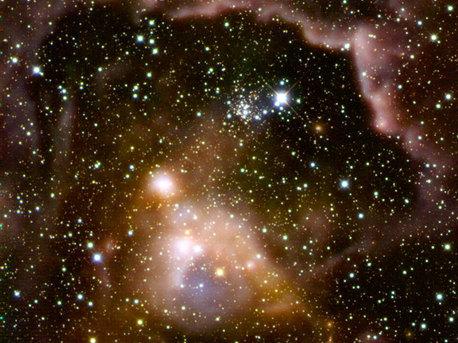 Aufnahme der Sternentstehungsregion ISOSS J22164+6003 im Infrarotlicht: Massereiche Sterne in frühen Phasen ihrer Entwicklung. Einige der Protosterne sind noch tief in bis zu -255 Grad Celsius kaltes Gas und Staub eingebettet und nur im fernen Infrarot nachweisbar. Kombination von HERSCHEL-Beobachtungen im fernen Infrarot (rötliche und gelbliche Strukturen) mit einem Bild im nahen Infrarot (Calar-Alto-Observatorium).