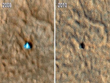 Two images of the Phoenix Mars lander taken from Martian orbit in 2008 and 2010. The 2008 lander image (left) shows two relatively blue spots on either side corresponding to the spacecraft's clean circular solar panels. In the 2010 (right) image scientists see a dark shadow that could be the lander body and eastern solar panel, but no shadow from the western solar panel.