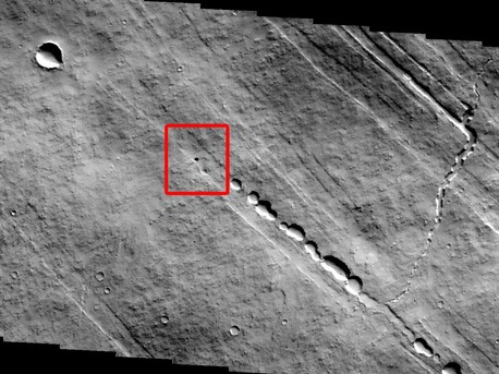 The small round black spot in this THEMIS image may be a hole in the roof of a Martian lava tube or cave.