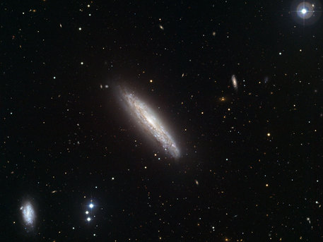 "This visible light image, made with the Wide Field Imager on the MPG/ESO 2.2-metre telescope at the La Silla Observatory in Chile, shows the galaxy NGC 4666 in the centre. It is a starburst galaxy, about 80 million light-years from Earth, in which particularly intense star formation is taking place. The starburst is thought to be caused by gravitational interactions with neighbouring galaxies, including NGC 4668, visible to the lower left. A combination of supernova explosions and strong winds from massive stars in the starburst region drives a vast outflow of gas from the galaxy into space — a so-called ""superwind"". NGC 4666 had previously been observed in X-rays by the ESA XMM-Newton space telescope, and these visible light observations were made to target background objects detected in the earlier X-ray images.