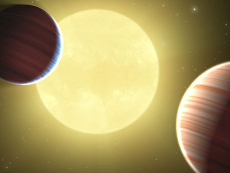 This artist's concept illustrates the two Saturn-sized planets discovered by NASA's Kepler mission. The star system is oriented edge-on, as seen by Kepler, such that both planets cross in front, or transit, their star, named Kepler-9. This is the first star system found to have multiple transiting planets.