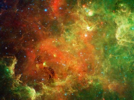 """This swirling landscape of stars is known as the North American nebula. In visible light, the region resembles North America, but in this new infrared view from NASA's Spitzer Space Telescope, the continent disappears.  Where did the continent go? The reason you don't see it in Spitzer's view has to do, in part, with the fact that infrared light can penetrate dust whereas visible light cannot. Dusty, dark clouds in the visible image become transparent in Spitzer's view. In addition, Spitzer's infrared detectors pick up the glow of dusty cocoons enveloping baby stars.  Clusters of young stars (about one million years old) can be found throughout the image. Slightly older but still very young stars (about 3 to 5 million years) are also liberally scattered across the complex, with concentrations near the """"head"""" region of the Pelican nebula, which is located to the right of the North American nebula (upper right portion of this picture).  Some areas of this nebula are still very thick with dust and appear dark even in Spitzer's view. For example, the dark """"river"""" in the lower left-center of the image -- in the Gulf of Mexico region -- are likely to be the youngest stars in the complex (less than a million years old).  The Spitzer image contains data from both its infrared array camera and multiband imaging photometer. Light with a wavelength of 3.6 microns has been color-coded blue; 4.5-micron light is blue-green; 5.8-micron and 8.0-micron light are green; and 24-micron light is red."""