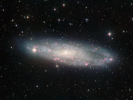 Diese Aufnahme, die mit dem MPG/ESO 2,2-Meter-Teleskop am La Silla-Observatorium in Chile aufgenommen wurde, zeigt die stark seitlich gekippte Spiralgalaxie NGC 247 vor einem reichhaltigen Hintergrund und lässt feine Details sichtbar werden. Die Astronomen gehen davon aus, dass die von der Erde aus gesehen starke Neigung dieser bekannten Galaxie der Grund dafür ist, dass ihre Entfernung bisher immer überschätzt wurde.