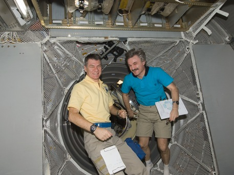 ESA astronaut Paolo Nespoli (top) and Russian cosmonaut Alexander Kaleri, both Expedition 26 flight engineers, work in the newly-attached ESA's ATV Johannes Kepler of the International Space Station. NASA photo iss026e029705.