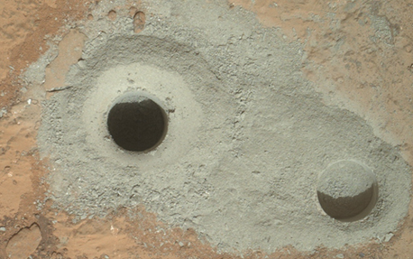 "At the left of this image from NASA's Curiosity rover is the hole in a rock called ""John Klein"" where the rover conducted its first sample drilling on Mars. Image credit: NASA/JPL-Caltech/MSSS"